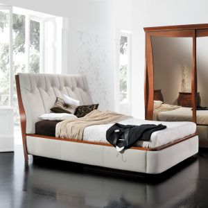 Piękne, białe łóżko z nietypowo tapicerowanym zagłówkiem. Wykończenie drewnianymi elementami dodaje mu jeszcze większej elegancji. Fot. Paged Meble