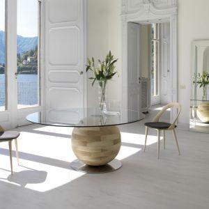 """Stół """"Gheo""""ma okrągły, szklany blat, który umieszczony został na drewnianej, wielkiej kuli. To pięknie i bardzo nowoczesne połączenie. Fot. Porada"""