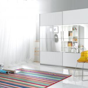 Beta to biała szafa z drzwiami przesuwnymi, na których środku zamocowano lustra. Dzięki jasnej barwie i lustrom, szafa dodaje pomieszczeniu przestrzenności. Fot. Helvetia Wieruszów