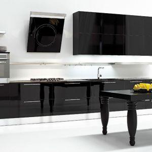 Czerń i biel to największe przeciwieństwo, ale i najbardziej zgrana para. Całkowicie czarna, utrzymana w wysokim połysku zabudowa kuchenna na tle śnieżnobiałej ściany prezentuje się cudownie. Warto zwrócić uwagę także doskonale dopasowany stół ze stylowymi nogami Fot. Aran Cucine