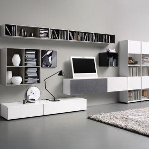Biały system naścienny do nowoczesnego salonu. Znajduje się w nim miejsce zarówno do przechowywania przedmiotów dekoracyjnych, jak i tych, które powinny być schowane. Fot. BoConcept