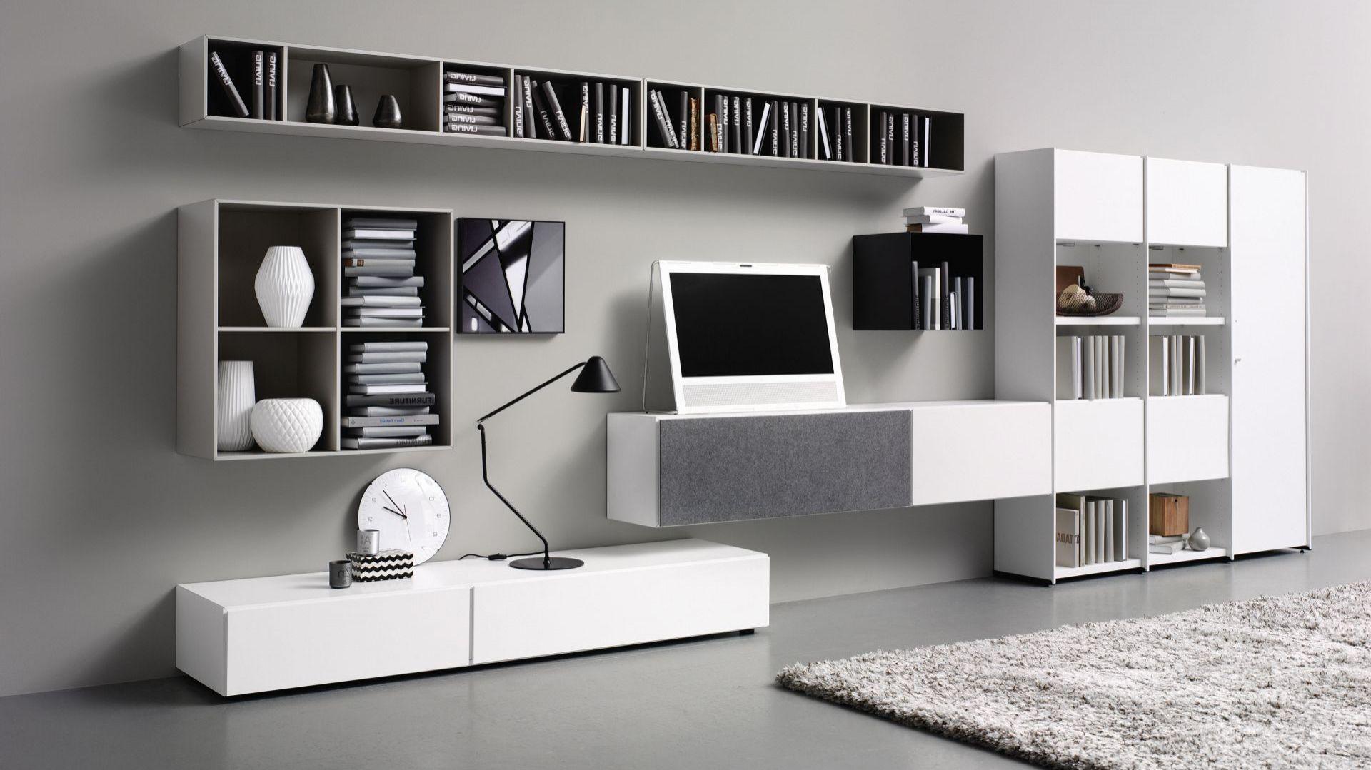 Biały system naścienny to nowoczesnego salonu. Znajduje się w nim miejsce zarówno do przechowywania przedmiotów dekoracyjnych, jak tych, które powinny być schowane. Fot. BoConcept
