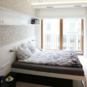 Nieduża sypialnia, która mieści w sobie wygodne łóżko wcale niemałych rozmiarów. Półki umieszczone na ścianie pozwalają na przechowywanie książek czy też płyt, ale nie zabierają przestrzeni z pokoju. Projekt: Monika i Adam Bronikowscy. Fot. Bartosz Jarosz