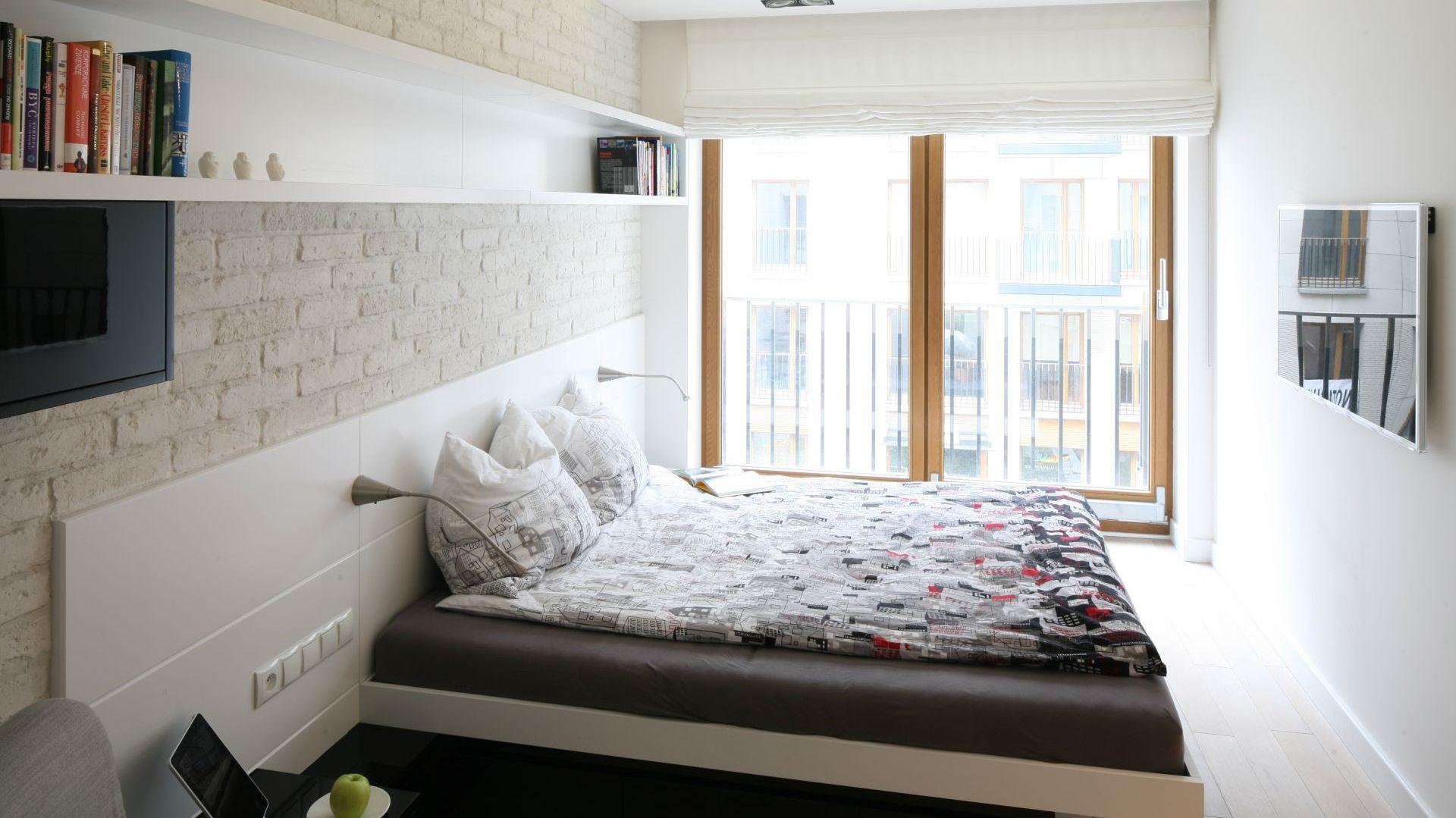 Nieduża sypialnia, która mieści w sobie wygodne łóżko wcale nie małych rozmiarów. Półki umieszczone na ścianie pozwalają na przechowywanie książek czy też płyt, ale nie zabierają przestrzeni z pokoju. Proj.Hola Design. Fot.Bartosz Jarosz