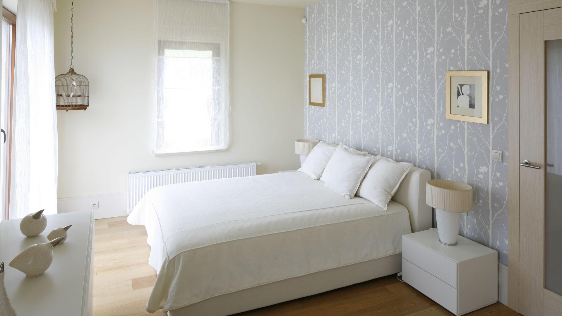 Białe łóżko usytuowane centralnie na największej ścianie w sypialni, która jednocześnie stanowi najbardziej widoczny element w pokoju, ponieważ została udekorowana tapetą. Projekt: Małgorzata Borzyszkowska. Fot.Bartosz Jarosz