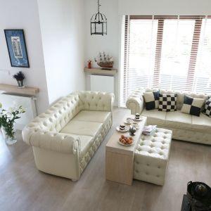 W salonie o większej powierzchni możemy sobie pozwolić na nie jedną sofę, ale nawet na dwie. W tym domu postawiono na model a\'la chesterfield. Projekt: Jarosław Jończyk, Monika Włodarczyk. Fot. Bartosz Jarosz