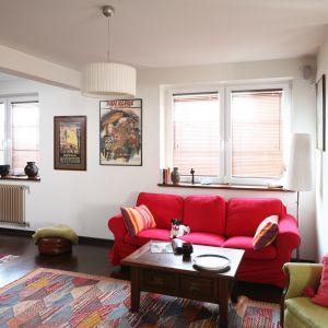 Jasny salon ocieplony soczystymi kolorami. Jednak najbardziej uwagę zwraca miękka sofa w czerwonym kolorze. Projekt: Magdalena Misaczek. Fot. Bartosz Jarosz