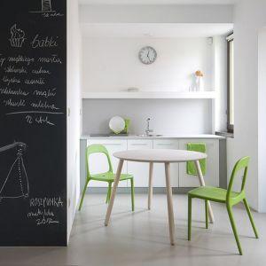 Mała, biała kuchnia bez górnej zabudowy. Rozwiązanie dobre dla tych, którzy zbyt często nie gotują. W małej kuchni znalazło się jednak miejsce na stół i krzesła. Fot. Miloni