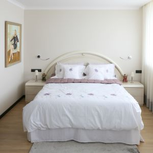 Jasna sypialnia zaaranżowana z przewagą bieli. Ciekawym elementem wnętrza jest duże łoże z dekoracyjnym zagłówkiem i nocnymi półeczkami, które tworzą synchroniczną całość. Projekt: Izabella Korol. Fot. Bartosz Jarosz
