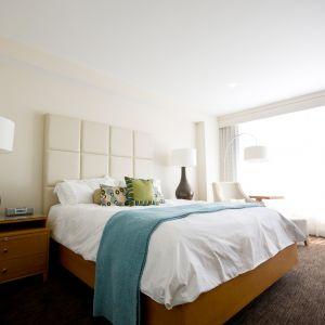 Jasne, kremowe ściany i wysoki zagłówek przypominający tabliczkę białej, słodkiej czekolady to doskonała propozycja do przytulnej, ale nowoczesnej sypialni. Fot. Home Sweet Home
