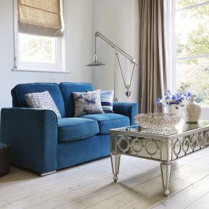 Mała sofa w turkusowym kolorze świetnie sprawdzi się w jasnym, niewielkim salonie. Miękkie siedzisko pozwoli na długie posiadówki, zaś kolorowe poduszki dodadzą nastrojowego wyglądu. Fot. Furniture Village