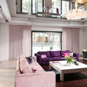 Do salonów z szerokimi oknami lub z wyjściem na taras znakomicie się prezentują jedna lub dwie sofy otaczające prosty, gustowny stolik. Możemy też dodać elementy w nietypowym kolorze. W tym przypadku projektant postawił na fiolet i róż. Projekt: Małgorzata Szajbel-Żukowska. Fot. Bartosz Jarosz