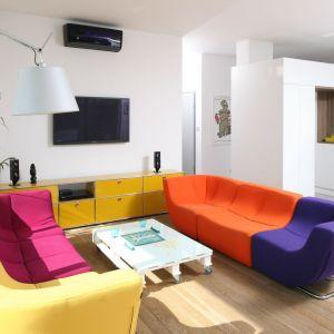 Żółta komoda i wielokolorowe sofy pięknie korespondują z białymi ścianami i urozmaicają nieco sterylne wnętrze. Jak widać, nowoczesny salon można urządzić również w kolorze. Projekt: Konrad Grodziński. Fot. Bartosz Jarosz