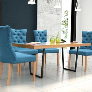 Krzesła obite niebieską, w części oparciowej pikowaną tkaniną świetnie komponują się z drewnianym stołem na metalowych nóżkach. Fot. Dom Art Styl