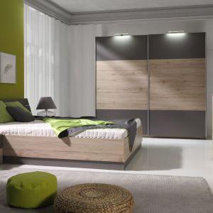 Sypialnia Dione wyróżnia się prostą formą oraz modną kolorystką. Połączenie szarej płyty z dekorem drewna jest aktualnie niezwykle na czasie. Fot. Maridex