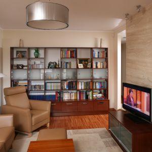 Są domy gdzie na biblioteczkę przeznacza się osobną przestrzeń, dla tych jednak którzy nie mogą sobie na to pozwolić, dobrym rozwiązaniem jest zagospodarowanie ściany w pokoju dziennym. Projekt: Piotr Gierałtowski Fot. Bartosz Jarosz