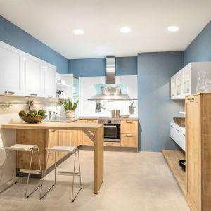 Biel z drewnem to wdzięczne połączenie. Jeśli chcemy, aby kuchnia wydawała się większa, zastosuj białe fronty na górze, zaś drewniane na dole. Fot. Max Kuchnie