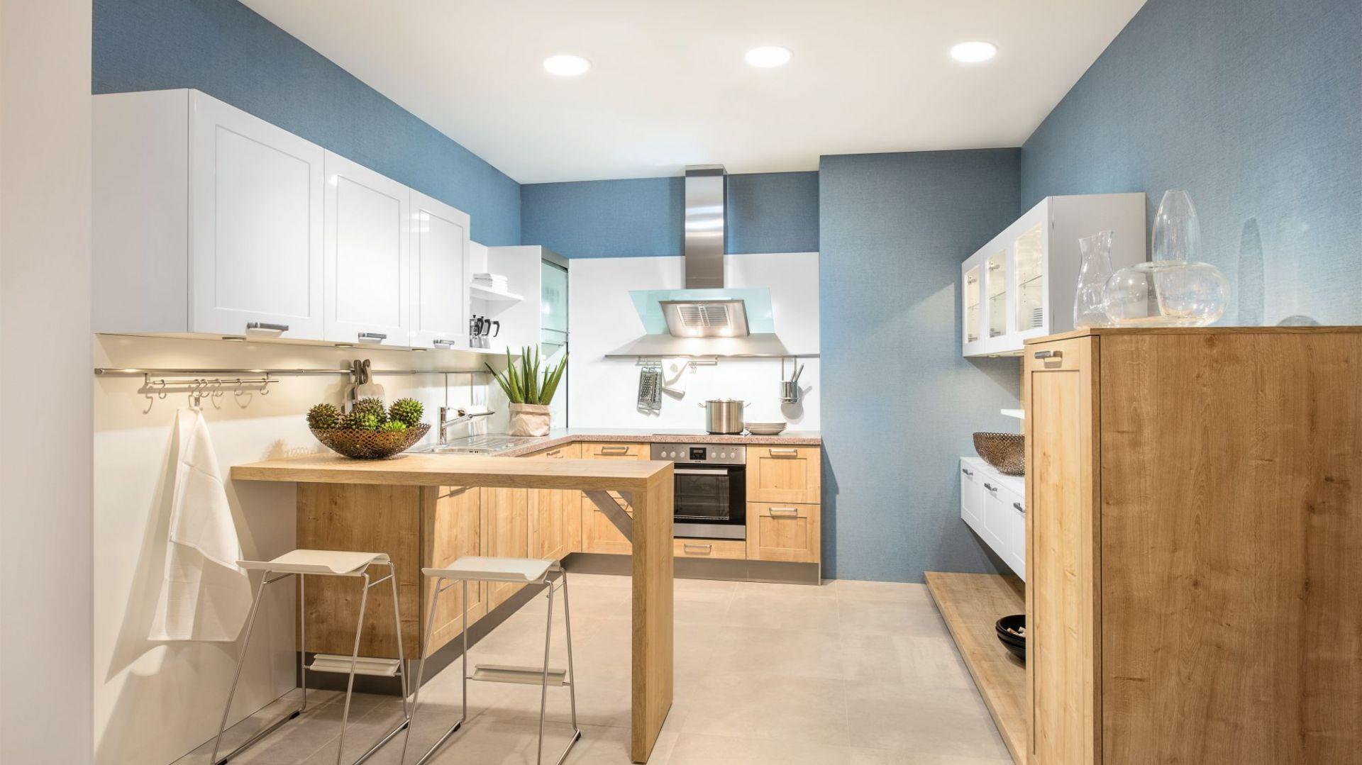 Drewniane szafki dolne znakomicie ocieplają surową w wyglądzie biało-niebieską aranżację i jasną zabudowę kuchni. Fot. Max Kuchnie