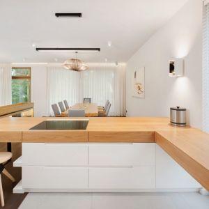 Najmodniejszym połączeniem w kuchni to biel i drewno. W większości projektów stosuje się go w formie: białe fronty + drewniany blat. To połączenie, które rozjaśnia aranżacje kuchni i wprowadza bardzo przytulny klimat. Projekt Razoo Architekci. Fot. Meluzyna Studio