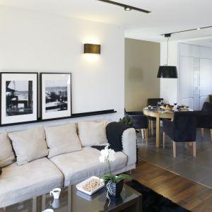 Dobrym sposobem na zachowanie harmonii we wnętrzu jest ustawienie między kuchnią a salonem stołu i krzeseł. Projekt: Małgorzata Mazur. Fot. Bartosz Jarosz