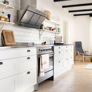 Aneksy kuchenne doskonale prezentują się bez górnej zabudowy. Półki umieszczone nad blatem, wsparte dekoracyjnymi podpórkami sprawiają, że kuchnia wygląda nowocześnie, ale też bardzo zwiewnie. Fot. Ballingslöv