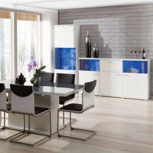 Jadalnia Morano marki Szynaka. Meble prezentuje się bardzo nowocześnie. Na uwagę zasługuje stół z jedną, masywną nogą oraz kolorowe oświetlenie w witrynach. Fot. Szynaka Meble