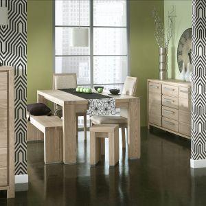 Jadalnia Oslno marki Dekort ma stół na grubych nogach do którego dopasowano ławy zamiast krzeseł. Fot. Dekort