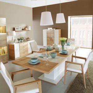 Jadalnia Modern marki Paged Meble łączy w sobie jasne ciepłe drewno i nieskazitelną biel. Ciekawym elementem jest słoneczne, złote oświetlenie w witrynach. Fot. Paged Meble