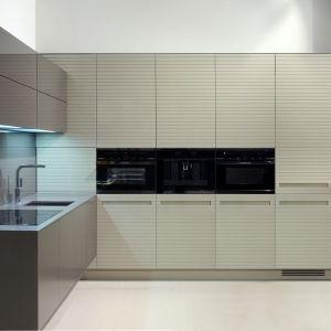 Kuchnia marki Remeb zaprojektowana została z myślą o małych powierzchniach. Fronty górnych szafek wykonane  ze szkła lakierowanego na szary kolor, otwierane są poprzez lekki dotyk. Fot. Remeb