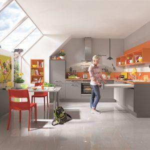Szara dolna zabudowa pięknie komponuje się intensywnymi kolorami. Pomarańczowe, otwarte półki zamiast górnej zabudowy sprawiają, że aranżacja prezentuje się wizualnie lekko. Fot. Nobilia