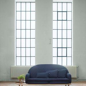 Delikatny kształt, który sprawdzi się w małych wnętrzach. Dzięki półce na której zostało umieszczone siedzisko obok sofy znajduje się także stolik. Fot. Fogia