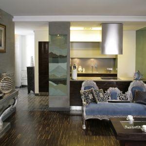 Najmocniejszym wizualnie elementem tego wnętrza jest stylowa, bogato zdobiona sofa oraz odpowiadająca jej wzorniczo konsolka. Eleganckie meble ciekawie kontrastują z nowoczesną kuchnią z tyłu. Projekt: Małgorzata Stachowiak Fot. Bartosz Jarosz