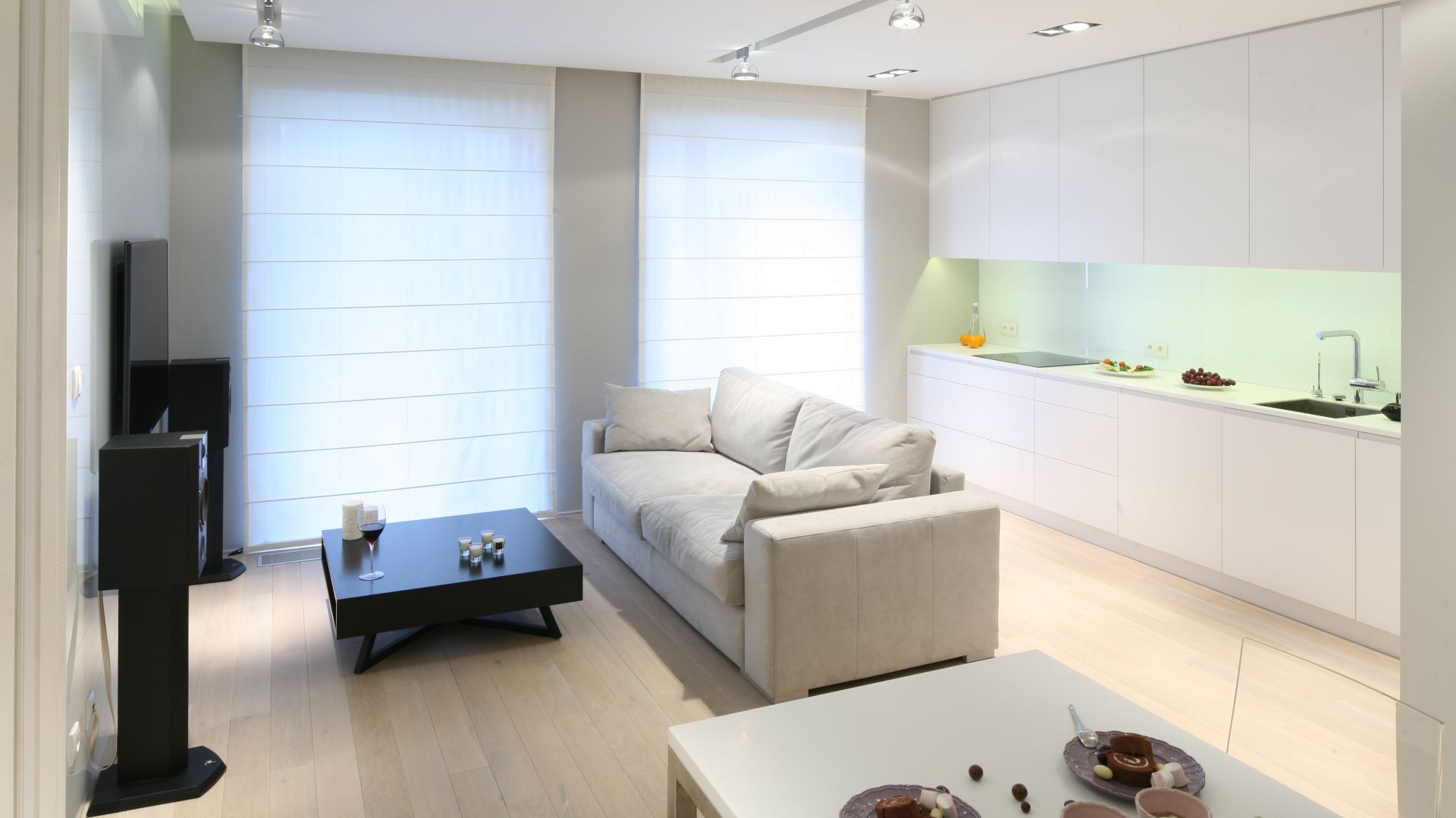 Salon połączony z kuchnią. Jasna kanapa w elegancki sposób dzieli obie strefy.  Duże okno sprawia, że pomieszczenie jest dobrze oświetlone i wydaje się wyższe. Projekt: Monika i Adam Bronikowscy Fot. Bartosz Jarosz