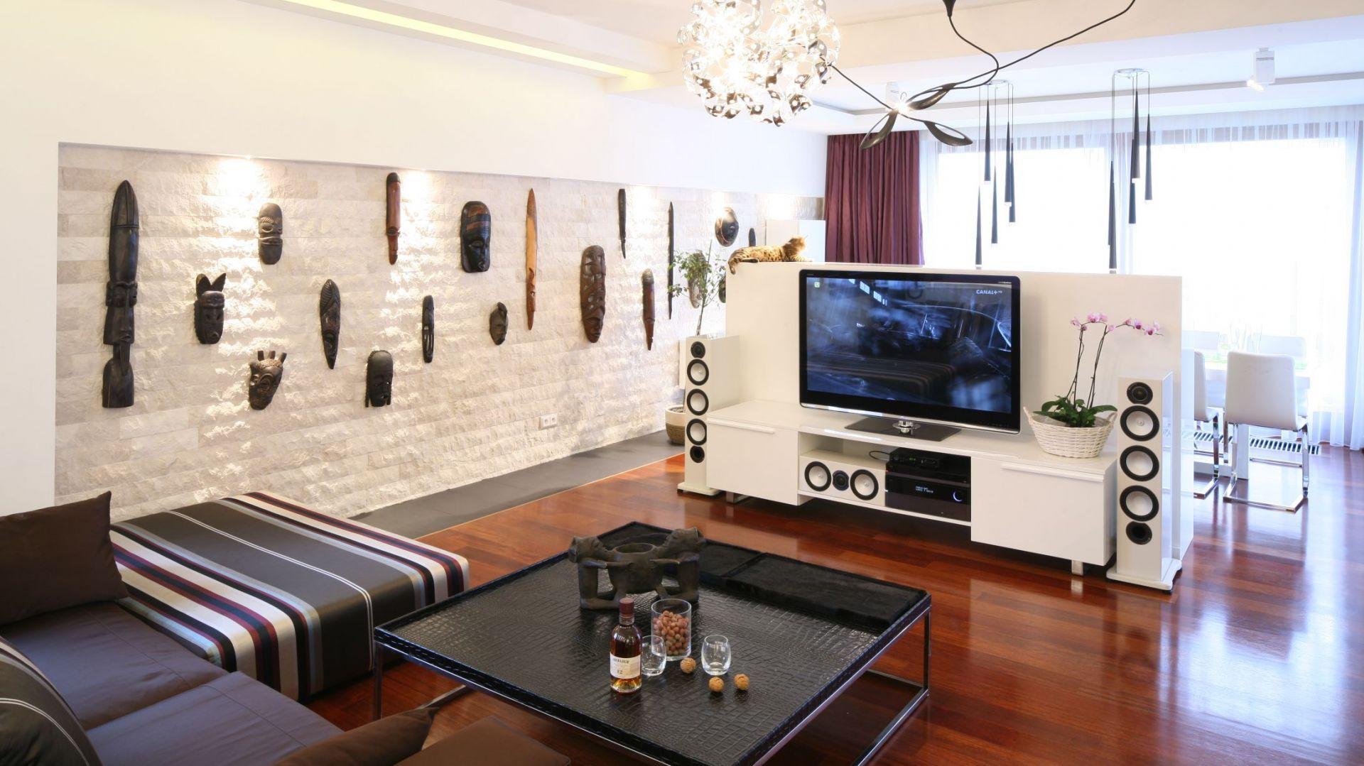 Telewizor umieszczony na specjalnej ściance może być doskonałą przegrodą rozdzielającą pomieszczenie. W tym mieszkaniu taką ścianką oddzielono salon od jadalni. Projekt: Katarzyna Mikulska-Sękalska. Fot. Bartosz Jarosz