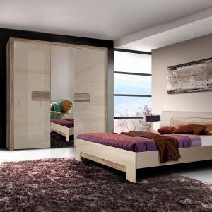 Sypialnia Tiziano ma jasne, ciepłe kolory, które doskonale nadają się do aranżacji przytulnej sypialni. Wąskie i wysokie lustro pomiędzy drzwiami w szafie  optycznie powiększy pokój. Fot. Meble Forte