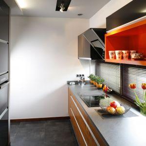 Pomarańczowe akcenty pasują do kuchni z ciemnymi frontami. Projekt: Anna Gruner Fot. Bartosz Jarosz