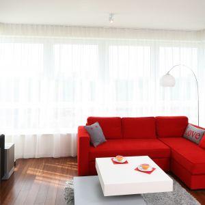 Niewielki salon urządzono w bieli i szarościach. Mocnym elementem wnętrza jest czerwony narożnik, który pięknie komponuje się z białą szafką RTV oraz biało-szarym stolikiem kawowym. Projekt: Izabela Szewc Fot. Bartosz Jarosz