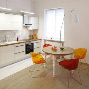 Otwarta kuchnia w białym kolorze jest neutralna dla reszty wnętrza. Aby bardziej ją ożywić, warto przy stole ustawić kolorowe krzesła. Projekt: Agnieszka Żyła. Fot. Bartosz Jarosz