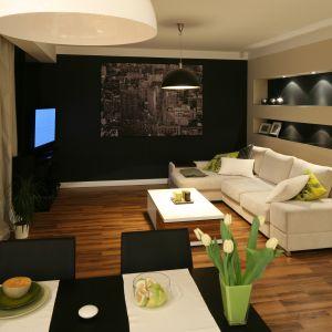 Salon dla wielbicieli oryginalnych aranżacji. Kolor czarny podkreśla nowoczesny charakter wnętrza. Choć zastosowany jest na wielu płaszczyznach wnętrze nie jest smutne ani ponure. A to za sprawą podświetlonych półek i dekoracji. Projekt: Lucyna Kołodziejska Fot. Bartosz Jarosz