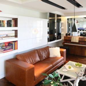 Oryginalnym akcentem tego wnętrza jest skórzana sofa w kolorze jasnego brązu, która sprawiła, że nieco sterylny, biały salon nabrał przytulności. Projekt: Małgorzata Mazur Fot. Bartosz Jarosz