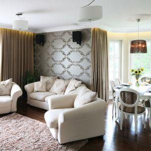 Do aranżacji efektownej jadalni wybrano środki najprostsze z możliwych - tapicerowane krzesła oraz biały stół na stylizowanych nóżkach tworzą niezwykle stylową aranżację. Zestaw jadalniany dobrze komponuje się też z elegancką, połyskującą tapetą. Projekt: Katarzyna Merta-Korzniakow Fot. Bartosz Jarosz