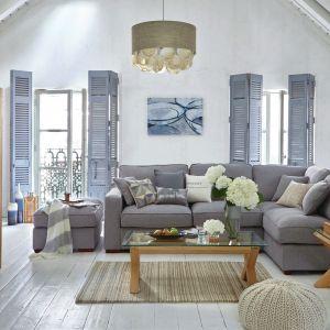 We wnętrzach w stylu marynistycznym oprócz bieli i błękitów nie może zabraknąć naturalnego drewna. Sofa w szarym kolorze doskonale współgra ze stolikiem na drewnianych nogach, o szklanym blacie. Fot. Dunelm