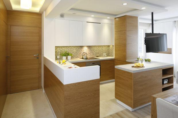 Biała kuchnia pięknie prezentuje się w duecie z drewnem. Sprawdź jak jasną, monochromatyczną kuchnię ocieplić drewnem.