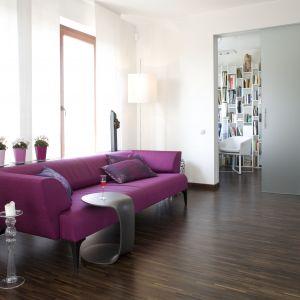 W salonie, który ma białe ściany dobrze jest postawić na detal w mocnym kolorze. Doskonałym rozwiązaniem będzie sofa odznaczająca się na tle całej aranżacji. Projekt: Małgorzata Szajbel-Żukowska. Fot. Marcin Onufryjuk