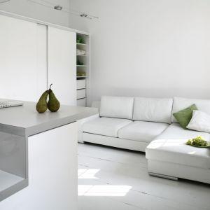 Biała kuchnia i biały salon prezentują się razem bardzo nowocześnie. Dla ożywienia aranżacji można zastosować żywe kolory w jednym lub drugim pomieszczeniu. Projekt: Liliana Masewicz-Kowalska. Fot. Bartosz Jarosz