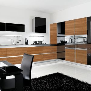 Drewno, czerń i stal to składniki tworzące stylową aranżację kuchni. Taką stylizację warto wyeksponować, otwierając ją na salon. Fot. Lube Cucine