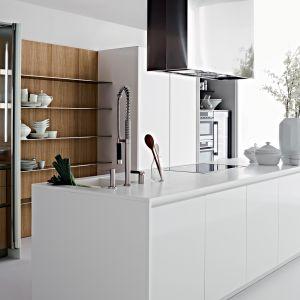 Fronty wykończone drewnem to sposób na ocieplenie i nadanie nowoczesnej kuchni nowego, bardziej charakteru. Dzięki wyspie ze strefami roboczymi, możemy pozwolić sobie na bardziej nietypową zabudowę pod ścianą. Fot. Elmar Cucine