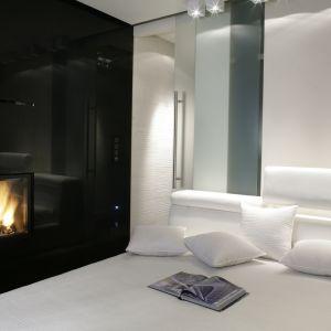 W tej sypialni białe, tapicerowane meble ciekawie kontrastują z czarną ścianą. Nie jest to jednak zwyczajna ściana, a system szaf z wbudowanym bio kominkiem. Projekt: Julita Chrząstek. Fot. Monika Filipiuk-Obałek