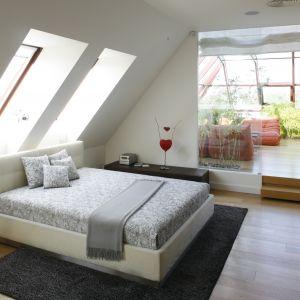 Przeszklone drzwi i widok na przytulny taras czyni tę sypialnię wyjątkową. Projekt: Alina Grzybowska, Konstanty Jeżewski. Fot. Bartosz Jarosz