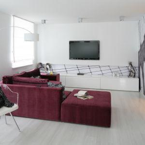 Urozmaiceniem minimalistycznego wnętrza, może być sofa w intensywnym kolorze. Na tle nieskazitelnej bieli doskonale prezentuje się soczysty śliwkowy fiolet. Projekt: Anna Maria Sokołowska. Fot. Bartosz Jarosz